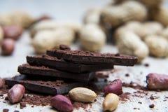 Mucchio di cioccolato fondente con le arachidi ed i gusci di noce Fotografie Stock Libere da Diritti
