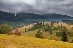 Mucchio di fieno sul prato della montagna con il cielo tempestoso drammatico L'Ucraina, Europa Immagine Stock Libera da Diritti