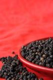 Mucchio di pepe nero su colore rosso Immagine Stock