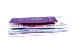 Mucchio di soldi investito nel loro passaporto Fotografie Stock