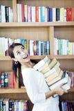 Mucchio di trasporto della donna dei libri Fotografia Stock
