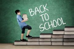 Mucchio di trasporto dello scolaro dei libri sulla scala Immagine Stock