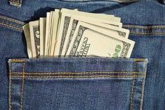 Mucchio di valuta americana degli Stati Uniti dei soldi, USD nella tasca posteriore delle blue jeans con la cucitura gialla come  Fotografia Stock Libera da Diritti