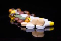Mucchio di varie pillole variopinte isolate sul nero Immagini Stock Libere da Diritti