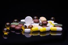 Mucchio di varie pillole variopinte isolate sul nero Fotografia Stock Libera da Diritti