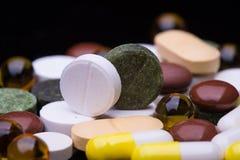 Mucchio di varie pillole variopinte isolate sul nero Immagine Stock Libera da Diritti