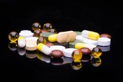 Mucchio di varie pillole variopinte isolate sul nero Fotografia Stock