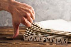 Mucchio di vecchi giornali accanto ai quadrati umani di rettangolo del cartone e della mano con la falsificazione scritta a mano  fotografia stock