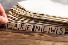 Mucchio di vecchi giornali accanto alle dita ed ai quadrati umani di rettangolo del cartone con le notizie false dell'iscrizione  immagini stock