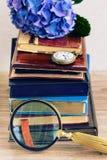 Mucchio di vecchi libri con i fiori e l'orologio Fotografie Stock Libere da Diritti