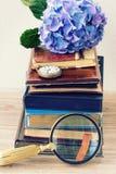 Mucchio di vecchi libri con i fiori e l'orologio Immagine Stock