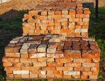 Mucchio di vecchi mattoni rossi sul pallet sul tramonto, fine su fotografie stock libere da diritti