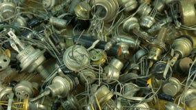 Mucchio di vecchie componenti radiofoniche, transistor del fondo dell'estremità del diodo con le lampadine principali video d archivio