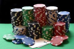 Mucchio ed assi rossi, blu, verdi, bianchi e neri dei chip di mazza Immagini Stock