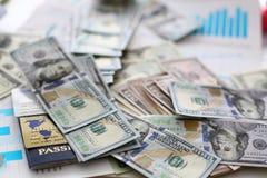 Mucchio enorme del passaporto e delle carte assegni dei soldi degli Stati Uniti che si trovano sui grafici finanziari di statisti fotografie stock