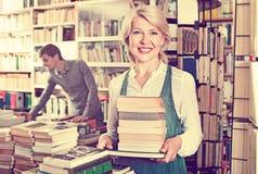Mucchio maturo sorridente del libro della tenuta della donna Fotografia Stock