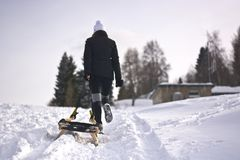The girl comes up with the toboggan. So much desired snow comes to the mountains and the woods royalty free stock photo