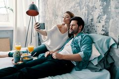 So much fun!. Beautiful young couple taking selfie and making faces while spending time in bed at home stock image