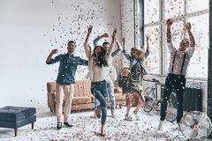 So much fun! Full length of happy young people dancing while spending time at home with confetti flying everywhere stock photography
