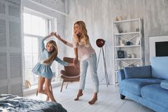 So much fun! Full length of mother and daughter holding hands an. D smiling while dancing in bedroom stock photos
