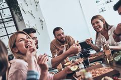 So much fun together!. Group of young people in casual wear eating and smiling while having a dinner party royalty free stock image