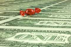 Much money. A red wraped candy on a sea of one dollar bills. With space for copy stock photos