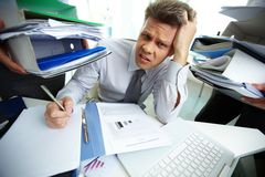 Much to do. Perplexed accountant looking at camera while doing financial reports Stock Image