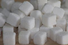 White sugar cubes on wooden desk stock photography