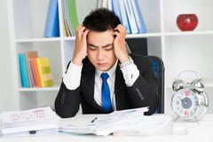 So much work to do!. Tired asian businessman sitting at table Stock Image