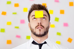 So much work to do!. Portrait of frustrated young man in formalwear and adhesive note on his forehead standing against the wall with many adhesive notes on it Stock Photography