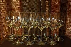 Mucha copa de vino vacía en orden en luz trasera de la tabla y del cobre como imágenes de archivo libres de regalías