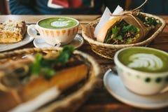 Mucha diversa comida en la tabla Desayuno sano en el restaurante: las tazas de té con leche verde llamaron Matcha Fotos de archivo libres de regalías