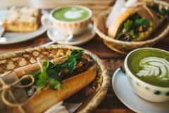 Mucha diversa comida en la tabla Desayuno sano en el restaurante: las tazas de té con leche verde llamaron Matcha Fotografía de archivo libre de regalías