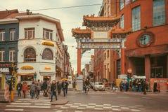 Mucha gente camina más allá de las puertas al área de la ciudad de China con las tiendas y los mercados étnicos imagenes de archivo