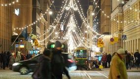 Mucha gente, decoraciones brillantes en la calle central de Helsinki durante celebraciones de la Navidad y ventas totales almacen de video