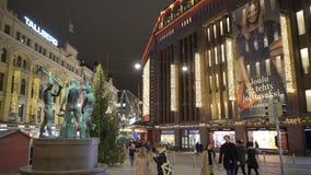 Mucha gente, decoraciones brillantes en la calle central de Helsinki durante celebraciones de la Navidad y ventas totales metrajes