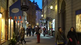 Mucha gente en las calles festivas de Estocolmo Decoraciones e iluminaciones del día de fiesta de la Navidad en el estrecho metrajes