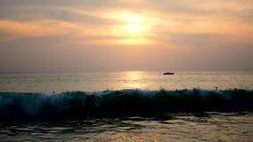 Mucha gente está balanceando en las ondas grandes por el mar en la puesta del sol metrajes