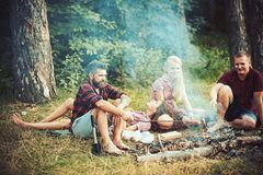 Mucha gente fríe las salchichas en los palillos de madera en la llama del fuego durante comida campestre en verano imagen de archivo