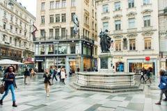 Mucha gente que camina en la parte central de capital austríaca con los edificios viejos y modernos Fotos de archivo libres de regalías