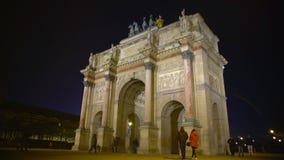 Mucha gente que camina por el arco triunfal du en el lugar Carrousel, noche París, Francia metrajes