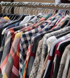 Mucha ropa en las suspensiones en un mercado de pulgas Imágenes de archivo libres de regalías
