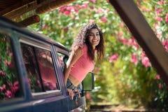 Muchacha árabe feliz que mira a escondidas hacia fuera la ventana de una furgoneta fotos de archivo