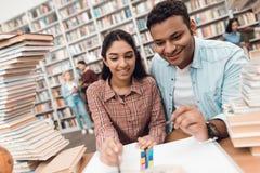 Muchacha étnica e individuo indios de la raza mixta rodeados por los libros en biblioteca Los estudiantes están tomando notas foto de archivo