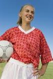 Muchacha (13-17) en bola de la explotación agrícola del kit del fútbol Imagen de archivo libre de regalías