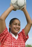 Muchacha (13-17) que lanza en balón de fútbol Fotos de archivo