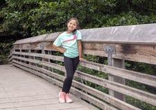 Muchacha año de diez Amerasian que presenta en un puente de madera en Washington Park Arboretum, Seattle, Washington fotografía de archivo