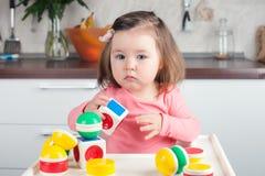 Muchacha 2 años con el pelo largo que juega con la construcción del diseñador en casa, a casa antes de entrenar Foto de archivo
