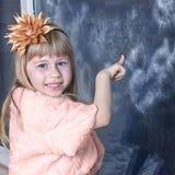Muchacha 5 años en vestido cerca de la ventana del invierno Imágenes de archivo libres de regalías