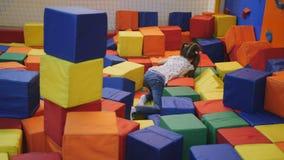 Muchacha 7 años que juegan en el centro del trampolín con los cubos coloreados suaves almacen de metraje de vídeo